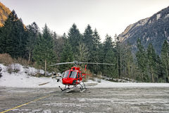 Red helicopter at swiss alpine heliport Stock Images