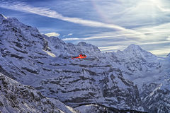 Red helicopter at swiss alps flying high Royalty Free Stock Photography