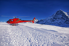 Red helicopter at swiss alps ski resort near Jungfrau mountain Royalty Free Stock Photo