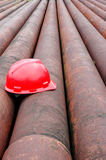 Red helmets of miners and iron pipe Royalty Free Stock Images