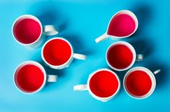 Red herbal tea in cups on blue background. Top view royalty free stock images