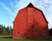 Red heritage barn. With woods in background and blue sky Stock Photo