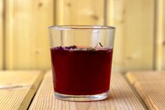 Red hibiscus tea in a glass cup royalty free stock images