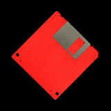 Red high density floppy disk. An old red high density floppy disk for computers against a black background stock photo