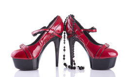 Red high heel female shoes with black necklace Royalty Free Stock Image