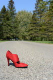 Red high heel shoe on road Royalty Free Stock Images
