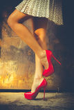Red high heel shoes. Woman legs in red high heel shoes and short skirt outdoor shot against old metal door Royalty Free Stock Image