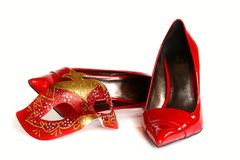 Red high-heeled shoes and carnival mask. Stock Images