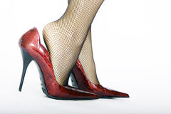 Red high heels. Female legs wearing fishnet stockings in red leather high heels Stock Image