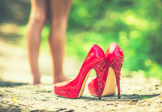 Red high heels with barefoot girl on background Royalty Free Stock Photos