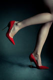 Red high heels on beautiful female legs stock photography