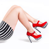 Red high heels on beautiful female legs Royalty Free Stock Photography