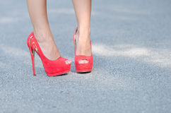 Red high heels. Close up on slim foot wearing bold red high heels fish mouth , straight and profile view on asphalt road. Horizontal photo royalty free stock photo