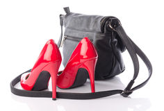 Red high heels shoes with a black handbag Royalty Free Stock Image