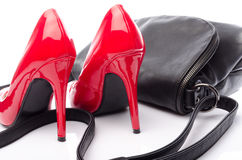 Red high heels shoes with a black handbag Stock Photos