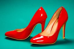 Red high heels shoes. Are on blue background stock image