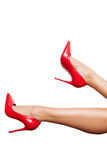 Red high heels shoes in perfect legs over white background Royalty Free Stock Photography