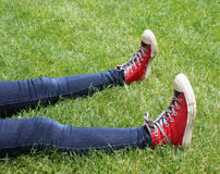 Red High Top Tennis Shoes in Green Grass. Playful bright red high top tennis shoes on jeaned legs in high green grass Stock Photography