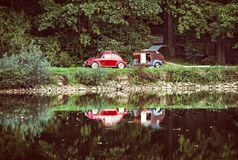 Red historic car with mini caravan is reflected, old filter. Red historic car with mini caravan is reflected in the lake. Travelling theme. Beautiful place. Old Royalty Free Stock Image
