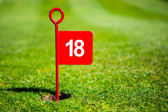 Red 18 hole golf flag. Red 18 18th hole golf flag sign on putting green with copyspace Stock Photos