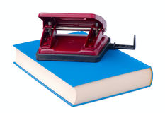 Red hole punch paper lies on the blue book Stock Image