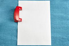Red hole puncher with empty sheet of paper, blue background. Royalty Free Stock Images