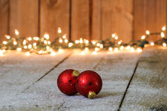 Red holiday ornaments with lights in background Royalty Free Stock Photography
