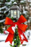 Red Holiday Ribbon on a yard light. Red Holiday Ribbon Christmas Decoration on a snow covered streetpost lamppost yard light Royalty Free Stock Photography