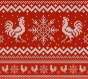 Red Holiday seamless pattern with knitted roosters and snowflakes. Christmas knitting scheme design. Cocks - symbol of Stock Images