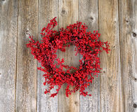 Red holly berry wreath on aged wooden boards Royalty Free Stock Photography