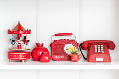 Red Home Related Decorative Objects in a White Shelf Royalty Free Stock Photography