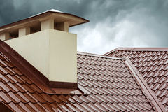 Red home roof. Red metal roof tile and smokestack Stock Image