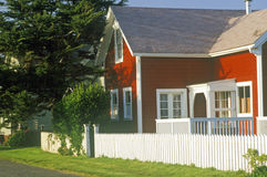 Red home with white picket fence Stock Photo
