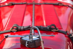 Red hood of an oldtimer. With leather belts to be fixed Stock Images
