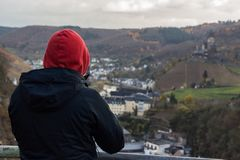 Red Hooded Man Looking over Village Valley Stock Images