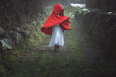 Red hooded woman on a dark country road stock images