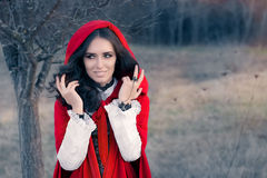 Red Hooded Woman Fairytale Portrait. Fairytale image of a beautiful girl wearing a red hood near the forest royalty free stock photography