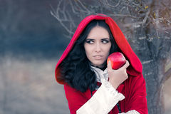 Red Hooded Woman Holding Apple Fairytale Portrait. Fairytale image of a beautiful girl wearing a red hood near the forest royalty free stock photography
