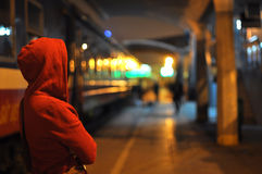 Red hooded. A young woman in a red hooded looking something in dark city royalty free stock image