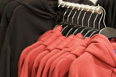 Red hoodies on hangers in a clothing store, close up stock photos