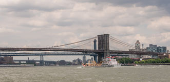 Red Hook barge passes under Brooklyn Bridge, East River, New Yor Royalty Free Stock Images