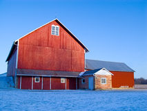 Red Hoosier barn in Winter. Red Indiana barn in winter farm scene catches late afternoon sunlight Royalty Free Stock Image