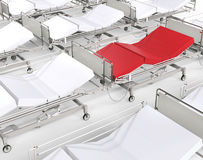 Red hospital bed stands out among many white beds Royalty Free Stock Image