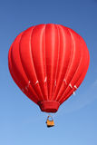 Red Hot Air Balloon. A bright red hot air balloon floating in a vivid blue sky Royalty Free Stock Image