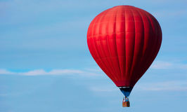 Red hot air balloon. With basket and people on board Royalty Free Stock Image