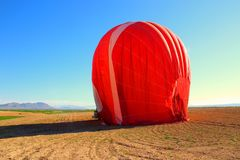 A red hot air balloon being dismantled. In the middle of a field Stock Photography