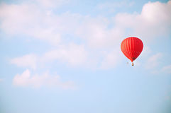 Red hot air balloon in blue sky with white clouds Stock Image