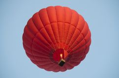 Red hot air balloon in a clear blue sky. royalty free stock images