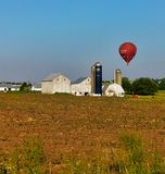 A red hot air balloon floating above farm buildings stock photos