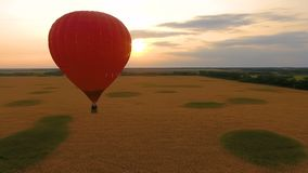 Red hot air balloon floating over field at sunset, romantic anniversary, love. Stock footage stock footage